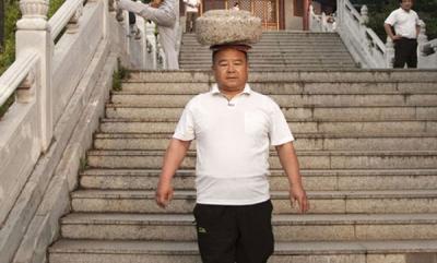 odd-news-man-exercises-40kg-stone-on-head-malayalam