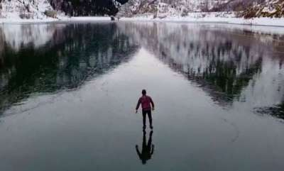 environment-drone-footage-of-ice-skater-on-frozen-dam-is-scary-but-so-stunning