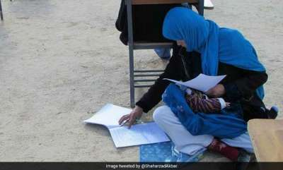 latest-news-afghan-woman-takes-exam-while-nursing-her-baby